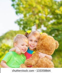 Two happy children enjoying big brown soft bear outdoors, brother and sister hugging, having fun on spring time, love and happiness concept
