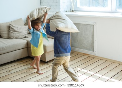 Two happy children is fighting a pillows each other at home