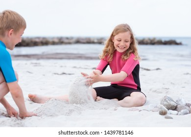 Two happy children in neoprene swimsuits playing on the beach with sand