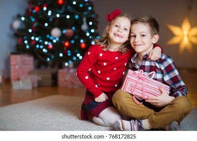 Two happy children in new year eve with presents near New Year Tree at home
