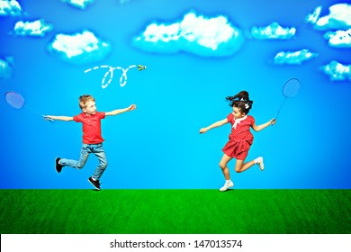 Two happy children playing badminton together over blue sky in a bright summer day.