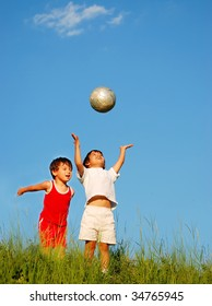 Two happy children playing with a ball on meadow