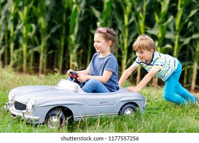 Two happy children playing with big old toy car in summer garden, outdoors. Boy driving car with little girl inside. Laughing and smiling kids. Family, childhood, lifestyle concept..
