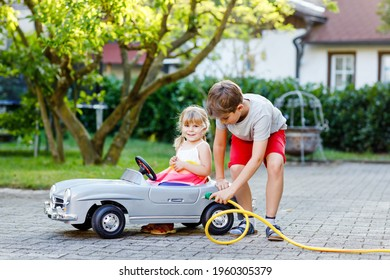Two happy children playing with big old toy car in summer garden, outdoors. Kid boy refuel car with little toddler girl, cute sister inside. Boy using garden hose and fill up with gasoline, sibling