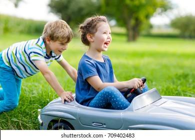 Deux enfants heureux jouant avec une grande vieille voiture en plein air dans le jardin d'été. Garçon poussant la voiture avec une petite fille à l'intérieur. Des enfants qui rient et sourient. Famille, enfance, concept de vie.