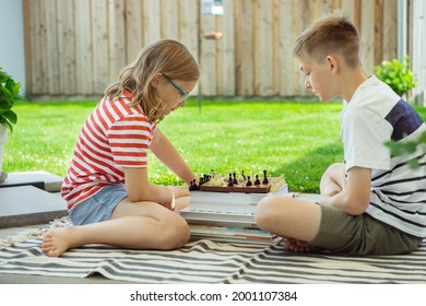 Two happy children playing chess on backyard at sunny day while summer holidays