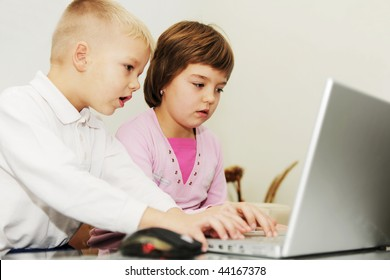 two happy children playing games and learning education lessons on laptop computer at home