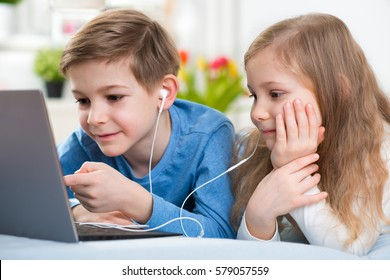 Two happy children playing with laptop and listening music with headphones in bed
