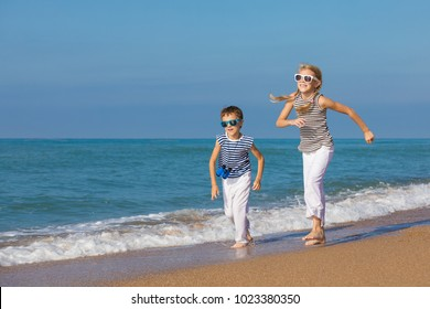 Two happy children playing on the beach at the day time. They are dressed in sailor's vests. Concept of sailors on vacation and friendly family.