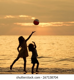 Two happy children playing on the beach at the sunset time