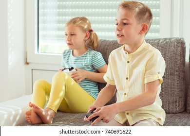 Two happy children playing video games with console at home