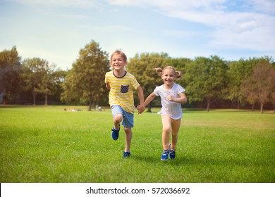 Two happy children running in summer park