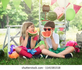 Two happy children are sitting outdoors eating watermelon fruit on grass and having fun. Use it for a summertime or healthy living concept.