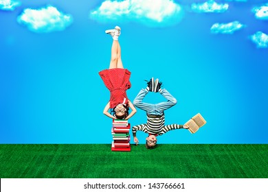 Two happy children standing on their heads on books. Educational concept.