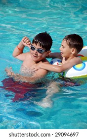 Two happy children in a swimming pool.Seven and thirteen years old .