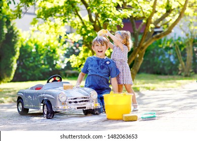Two happy children washing big old toy car in summer garden, outdoors. Brother boy and little sister toddler girl cleaning car with soap and water, having fun with splashing and playing with sponge.