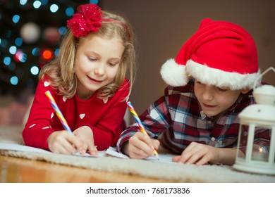 Two happy children writing letter at Christnas eve to Santa Claus at home near New Year tree