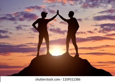 Two happy climbers on top of a mountain. Conceptual image of success