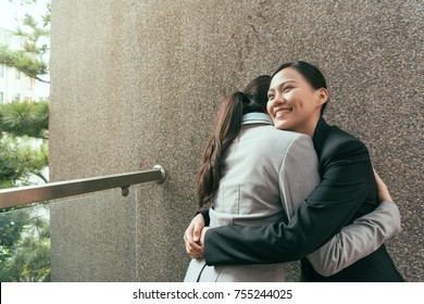 two happy confident Asian hugs together to celebrate the successful project finished outside of office.