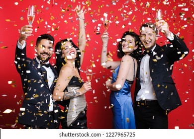 Two happy couples with glasses of champagne smiling and looking at camera while standing under falling confetti on red background. Couples celebrating holiday under confetti