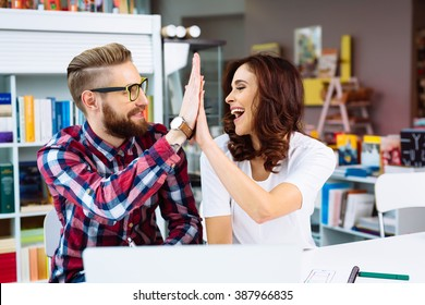 Two happy coworkers, designers making high  five in modern office