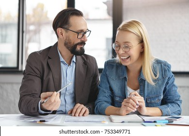 Two happy coworkers read market report, discuss financial matter, point in documents with pencils, sit at office desk. Married couple develop their own home business, share ideas about improvement