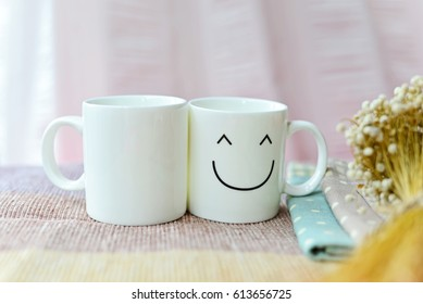 Two happy cups with dries flowers on the bed. Concept about love and relationship