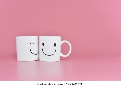 Two happy cups with marshmallows in the shape of heart on pink background. Concept about love and relationship. Creative colorful greeting card.Valentine Day with copy space for design work.