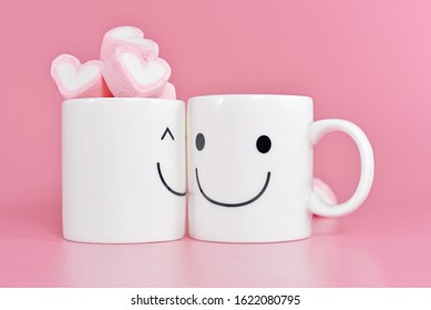 Two happy cups with marshmallows in the shape of heart on pink background. Concept about love and relationship. Creative colourful greeting card for Valentines Day.Happiness with lovely couple.