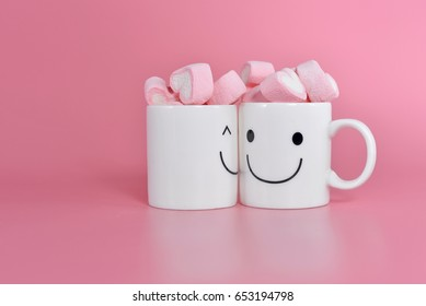 Two happy cups with marshmallows in the shape of heart on pink background. Concept about love and relationship. Creative colorful greeting card.