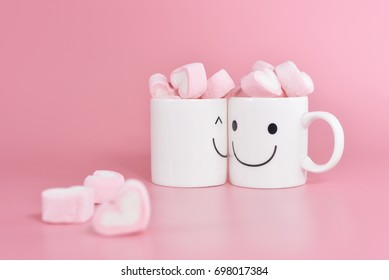 Two happy cups with marshmallows in the shape of heart on pink pastel background. Concept about love and relationship. Creative colorful greeting card. Lovely couple with happiness.
