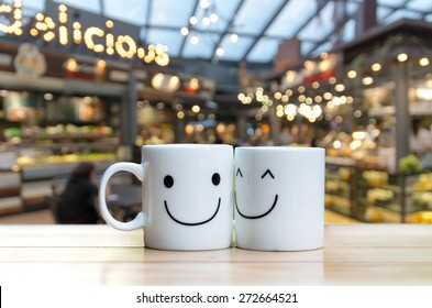 Two happy cups on coffee store blur background