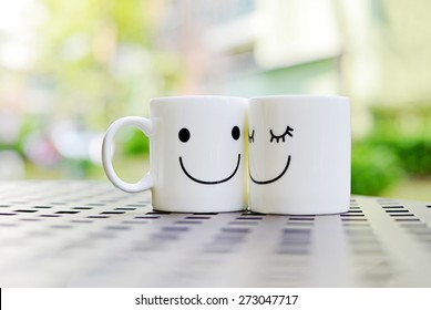Two happy cups on the table with nature background. Concept about love and relationship