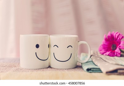 Two happy cups on the table with colorful polka dot tablecloth and pink flower. Concept about love and relationship (Vintage Style)