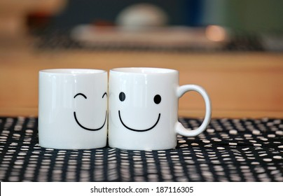 Two happy cups on wood table with black polka dot tablecloth. Concept about love and relationship
