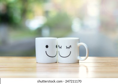 Two happy cups on wood table with bokeh, about love concept