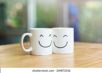 Two happy cups on the wood table, about love concept