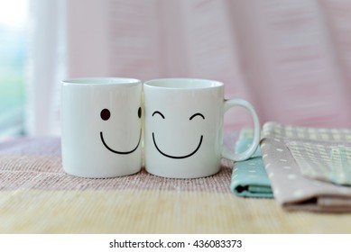 Two happy cups on wood table with colorful polka dot tablecloth. Concept about love and relationship.