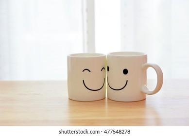 Two happy cups on wooden table. Concept about love and relationship.
