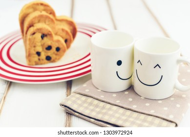 Two happy cups with polka dot tablecloth on the wooden table with chocolate cookies in shape of heart on white dish. Concept about love and relationship.Valentine idea.Together with happiness.