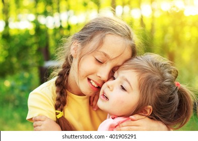 Two happy cute little girls hugs outdoor in spring garden. Kid sisters spending time together.