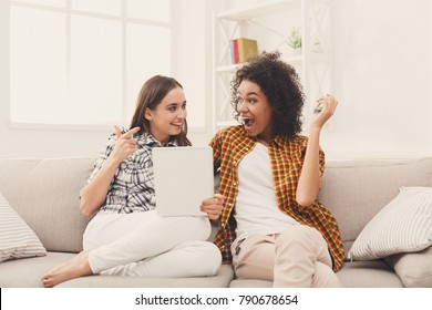 Two happy excited female friends using digital tablet. Laughing women browsing portable computer, celebrating win and sitting on couch at home, copy space