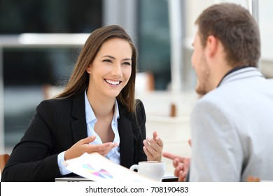 Two happy executives meeting in a restaurant and having a business conversation