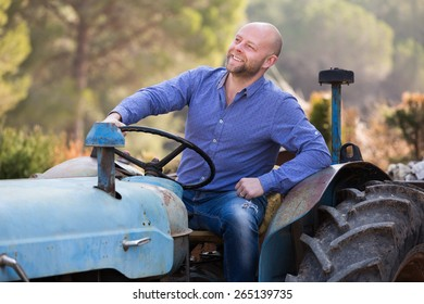 Two happy farmers talking near the agricultural machinery at shed