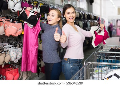 d83973940 two happy female customers holding bras and panties in hands in underwear  store