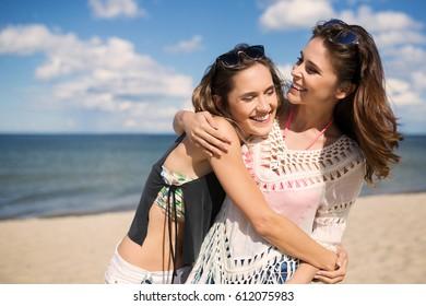 Two happy female friends hugging on beach