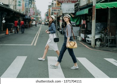 two happy female friends travelers with bags crossing street together outdoor sunny day in china town. japanese lady travel in chinese city walking on zebra cross in urban. girl wear hats look at sky.