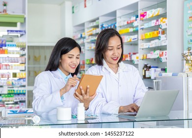 Two happy female pharmacists using computer and tablet for looking at prescription. Health care and medical concept.