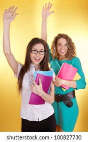 Two happy female students holding exercise books and rising their hands on a yellow background