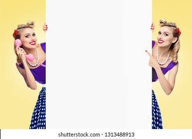 Two happy female twins, in pinup style dress with phone, showing blank signboard with copy space area for some slogan or advertising text message, over yellow background. Woman retro, vintage concept.